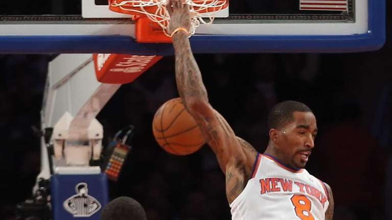 J.R. Smith dunks behind his head on a