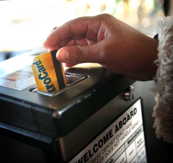 A rider inserts a metrocard into a fare