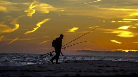 A man leaves the beach at sunset after