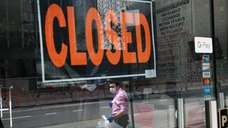 A closed sign displayed in the window of