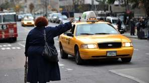 A woman tries to hail a taxi on