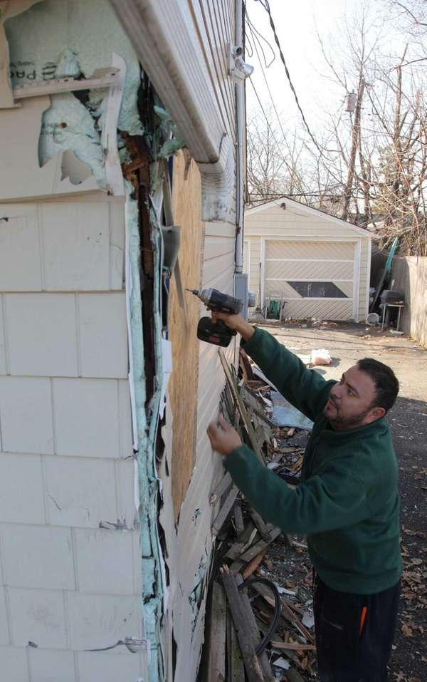 Cesar Campos works to board up a window