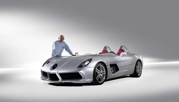 Sterling Moss stands next to a Mercedes-Benz SLR.