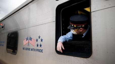 An LIRR conductor wears a mask as he