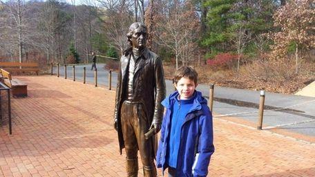 Harrison Kellogg McKenna stands alongside a statue of