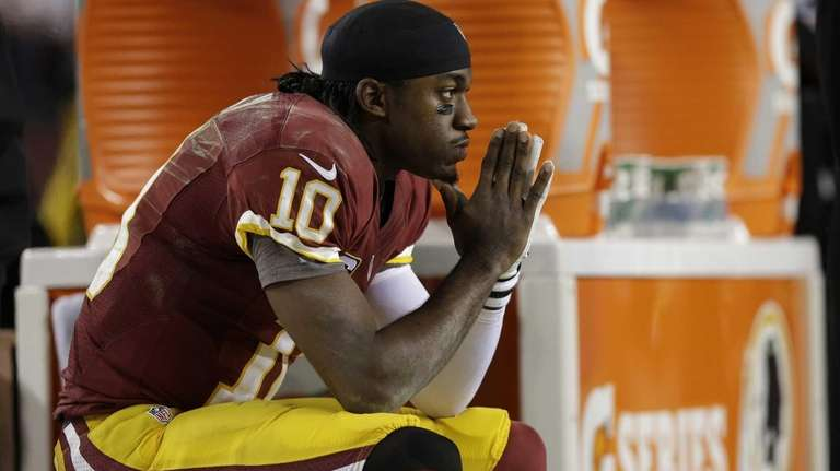 Washington Redskins quarterback Robert Griffin III sits on