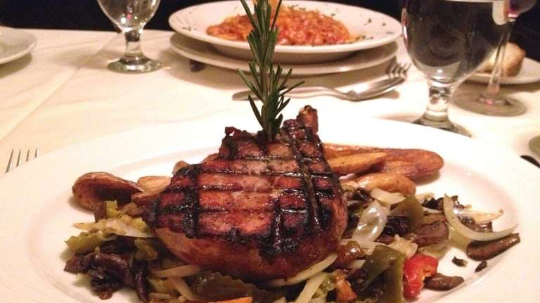 A center-cut pork chop garnished with hot peppers,