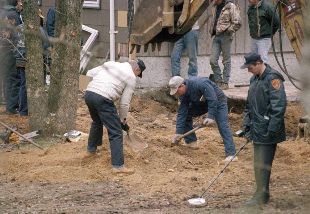 Workers sift through dirt as another scans with