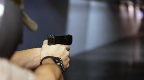 A man fires a handgun at Sandy Springs