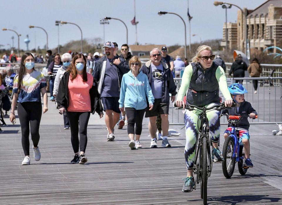 People walk along the boardwalk at Jones Beach