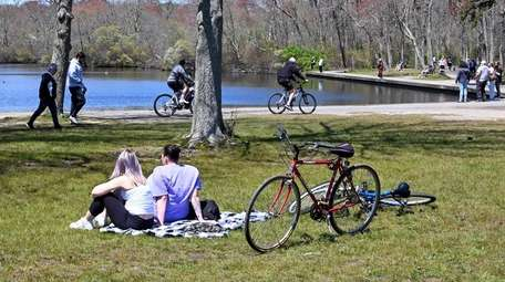 People riding bikes and walking at Belmont Lake