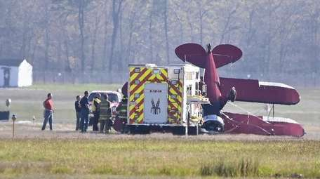 A small biplane flipped over on a runway