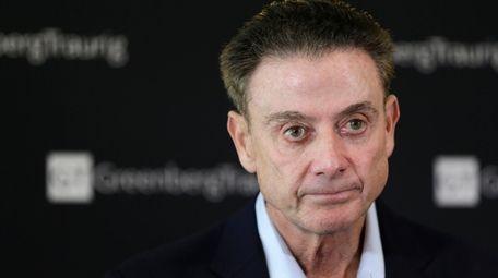 Former Louisville basketball coach Rick Pitino talks to