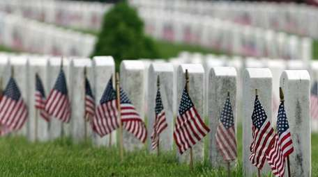 Gravestones are decorated with flags on Saturday at