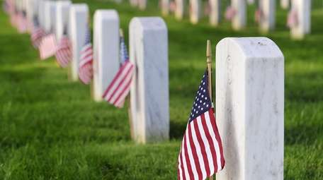 Flags placed by early risers are on graves