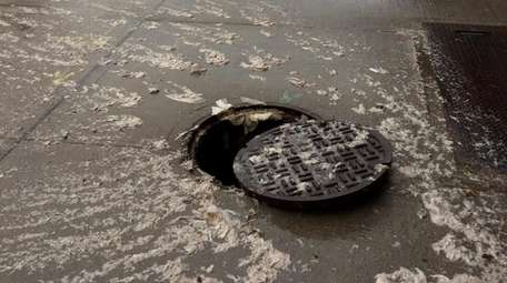 Wipes overflow out of a clogged manhole in