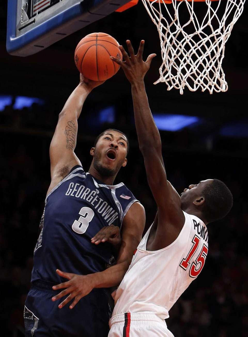 Georgetown's Mikael Hopkins attempts a dunk over St.