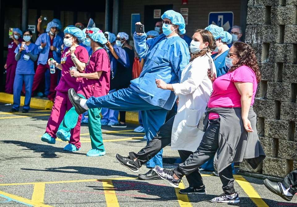 Healthcare workers form a kick line outside of