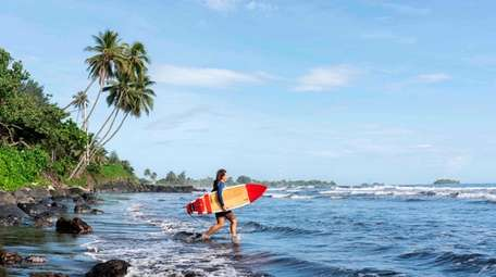 A surfer prepares to ride waves at the