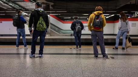 Commuters keep social distancing guidelines to prevent the