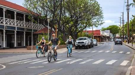 People wearing protective masks ride bicycles along Front