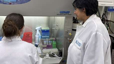 Chembio researchers perform a coronavirus test in the