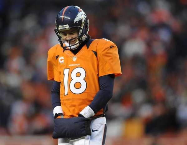 Denver Broncos quarterback Peyton Manning walks off the