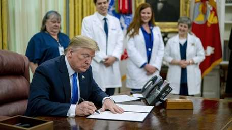 President Donald Trump signs a proclamation honoring National