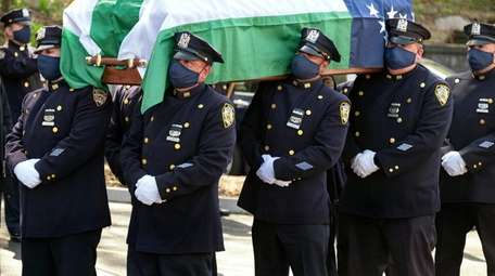In April, NYPD officers carry the coffin of