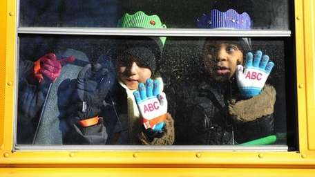 Children ride on a school bus in East