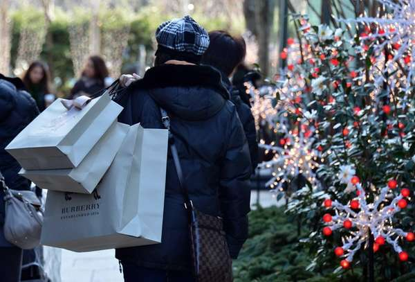 Holiday shoppers carry their last-minute purchases at the