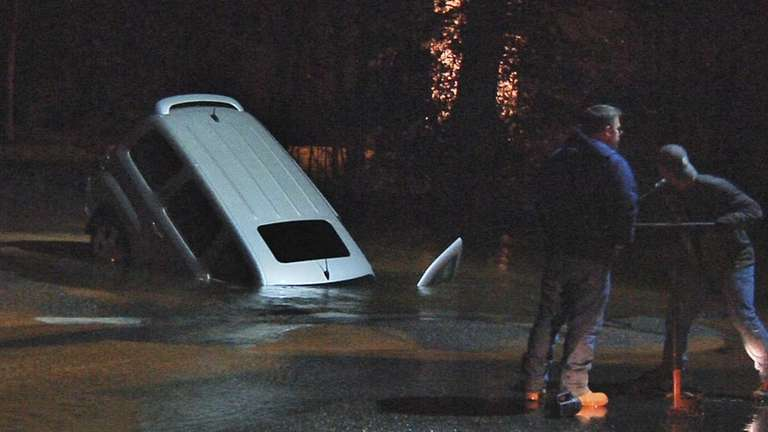 A vehicle sits partially submerged in a large