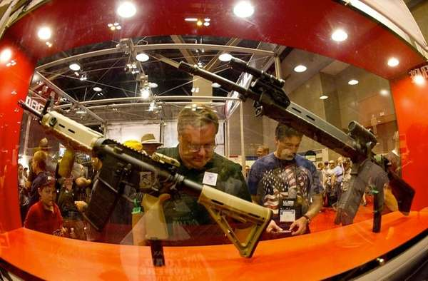 Gun enthusiasts look at various firearms on the