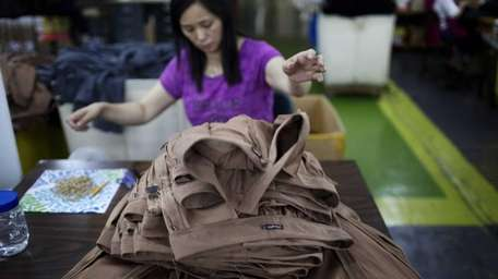 A button-sewer works on pants being manufactured at