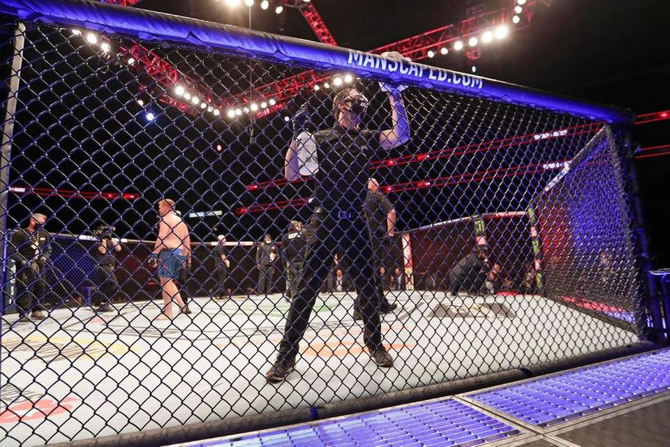 A worker wipes down the octagon between bouts