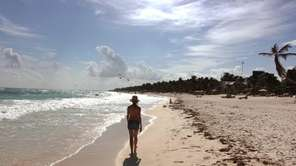 A woman walks along the beach in Tulum,