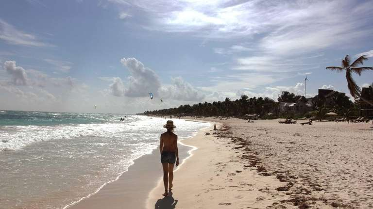 A woman walks along the beach in Tulum,