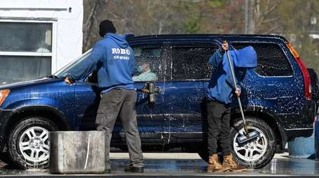 Workers from Robo Carwash clean a vehicle in
