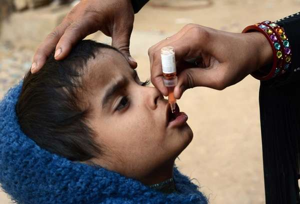 A Pakistani health worker administers polio vaccine drops