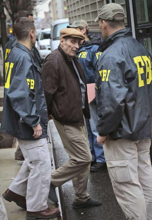 FBI and federal agents escort one of dozens