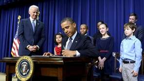 President Barack Obama signs an executive order beside