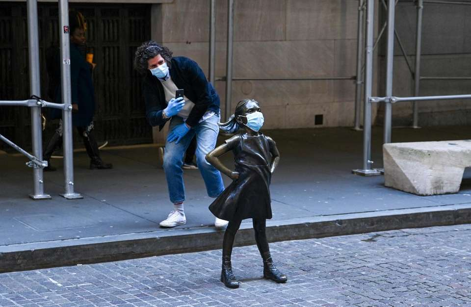 """A man takes pictures of the """"Fearless Girl"""