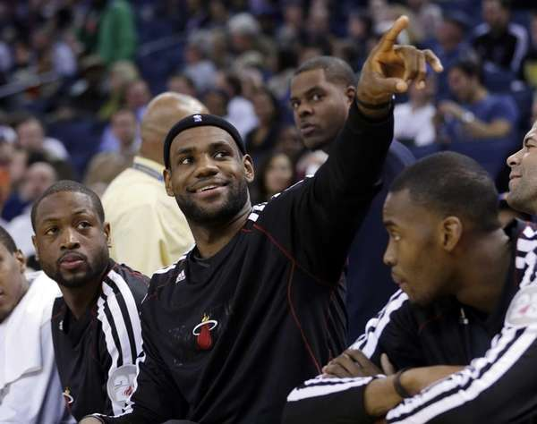 LeBron James, center, acknowledges fans in the stands