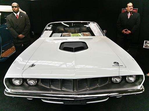 Security personnel stand near a rare 1971 Plymouth