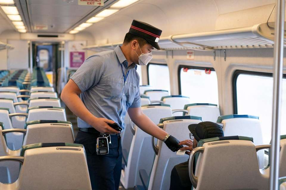A Long Island Rail Road conductor takes a