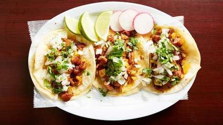 Al pastor tacos topped with cilantro and onions