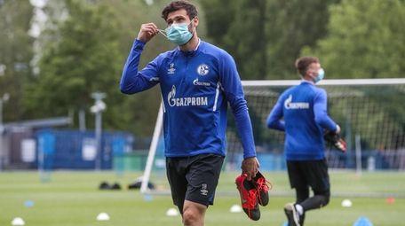 Schalke's German midfielder Daniel Caligiuri wears a face