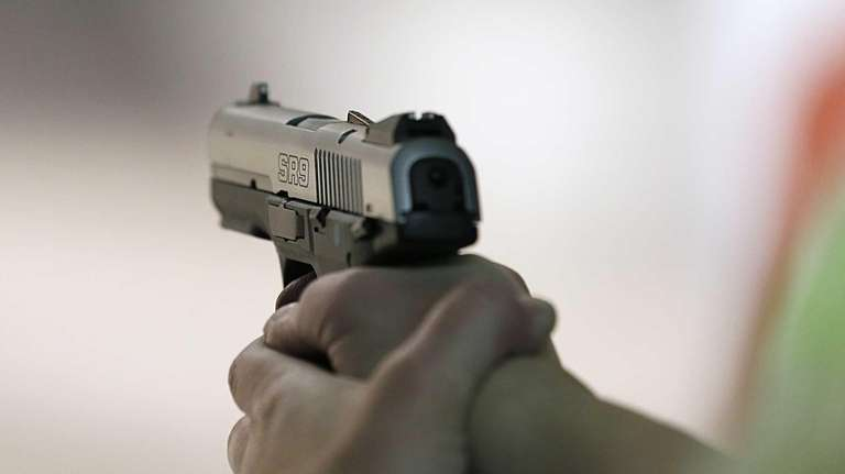 A women fires a handgun at the