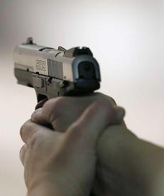 A women fires a handgun at the