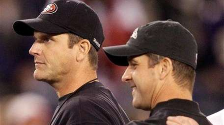 San Francisco 49ers head coach Jim Harbaugh, left,